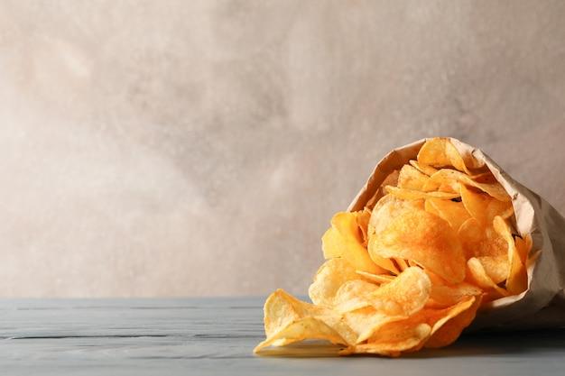 Saco de papel de batatas fritas no cinza de madeira, espaço para texto