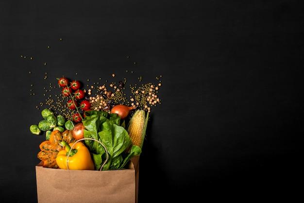 Saco de papel de compras cheio de diferentes legumes frescos em um fundo preto. conceito de compras. seleção orgânica de alimentos saudáveis. vista do topo. copie o espaço para texto.