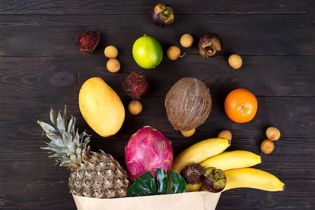 Saco de papel de diferentes frutas tropicais saudáveis no fundo escuro de madeira. vista do topo.