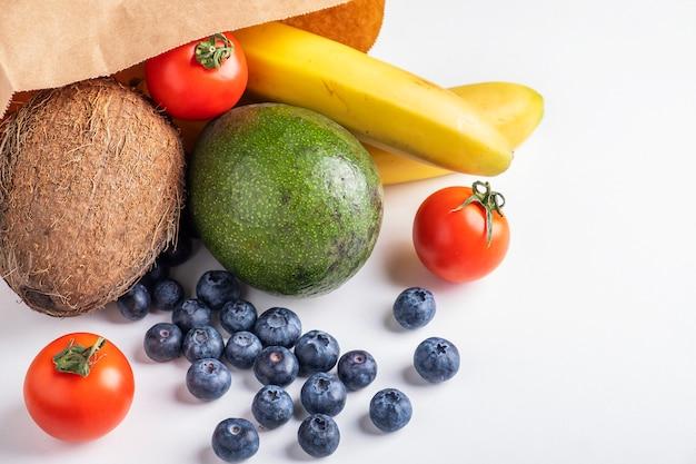 Saco de papel de loja com frutas e legumes na superfície branca