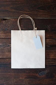 Saco de papel de maquete em papel kraft com etiqueta para presente em um fundo de madeira