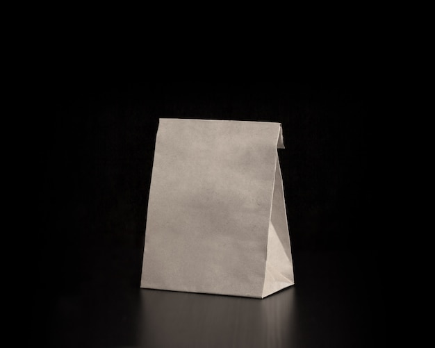 Saco de papel de ofício em branco sobre fundo de madeira. maquete de design responsivo.