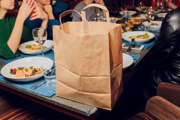 Saco de papel de sobremesa esperando pelo cliente no balcão no café moderno, entrega de comida, restaurante café, comida para viagem