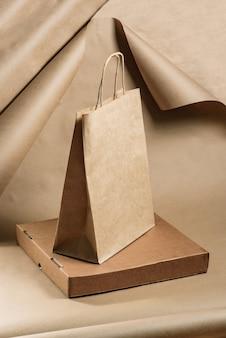 Saco de papel e caixa de pizza feitos de papelão em uma parede de papel artesanal.