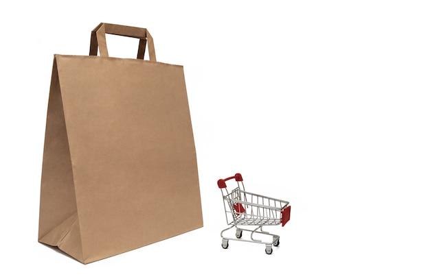 Saco de papel e carrinho de supermercado. o conceito de venda e compra de produtos.