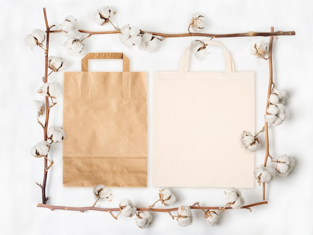 Saco de papel e saco de algodão dentro da moldura feita de ramos de flores de algodão no fundo branco