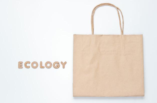 Saco de papel em uma superfície branca com a palavra ecologia.