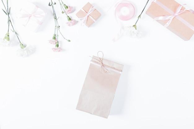 Saco de papel, flores, caixas com presentes e fitas na mesa branca, vista superior