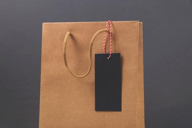 Saco de papel kraft com etiqueta de compra sexta-feira preta na superfície escura brilhante.