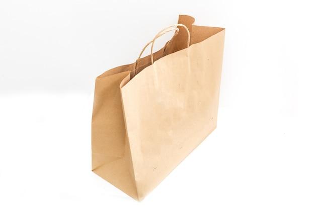 Saco de papel marrom claro vazio ofício em branco para take-away isolado no fundo branco. modelo de embalagem simulado. conceito de serviço de entrega. copie o espaço.