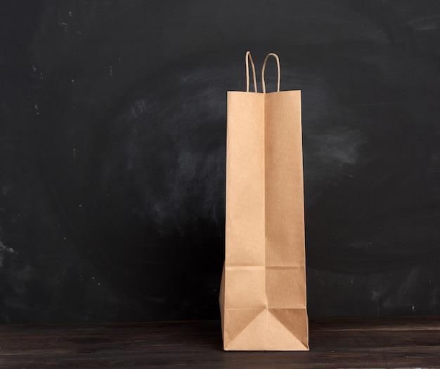 Saco de papel marrom com alças fica em um espaço de madeira