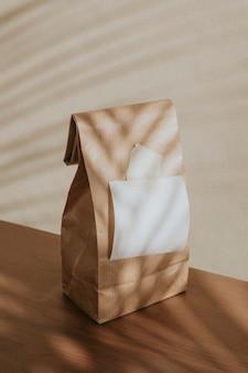 Saco de papel marrom com um papel branco em branco