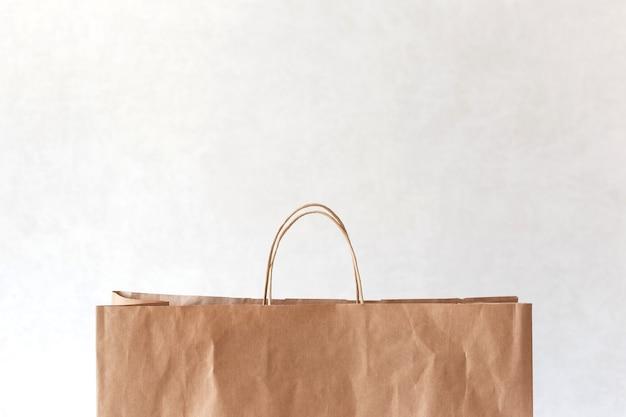 Saco de papel marrom em branco com espaço de cópia em cima na luz.