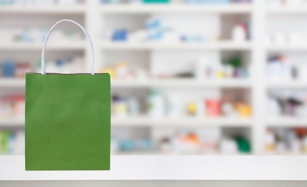 Saco de papel na mesa do balcão da farmácia da farmácia com medicamentos e produtos de saúde nas prateleiras