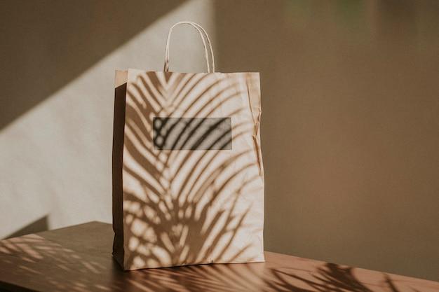 Saco de papel natural com sombra de folhas de palmeira