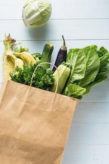 Saco de papel pardo com legumes e frutas