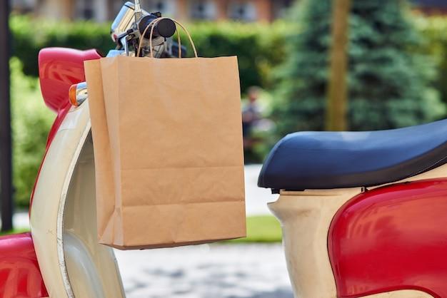 Saco de papel pendurado na scooter em pé conceito de serviços de entrega ao ar livre