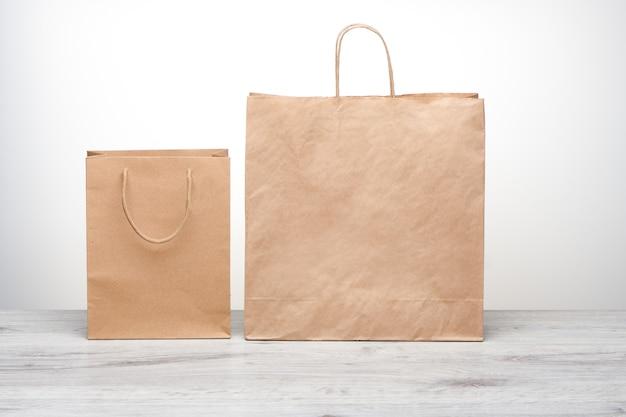 Saco de papel pequeno e grande com alças isoladas. maquete de saco de papel kraft na mesa de madeira. saco de compras reciclado para entrega em domicílio de produtos ou alimentos.