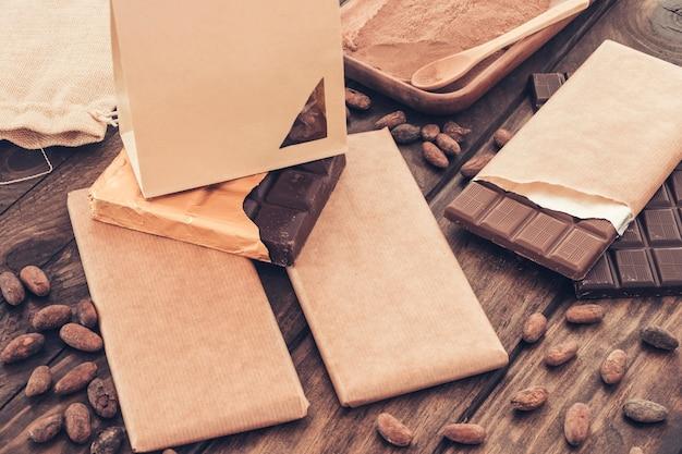 Saco de papel pequeno sobre a barra de chocolate embalada com grãos de cacau na mesa