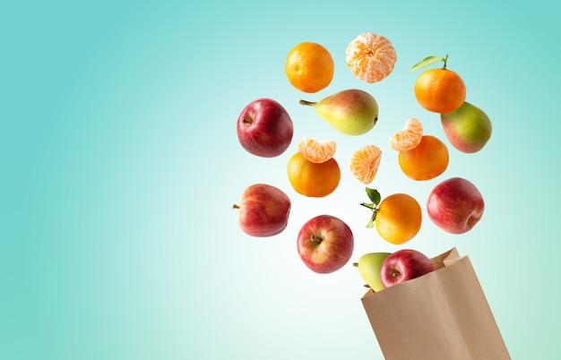 Saco de papel reciclável com frutas frescas voando