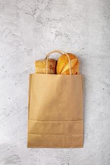 Saco de papel reciclável de supermercado com pães assados no fundo cinza com espaço de cópia