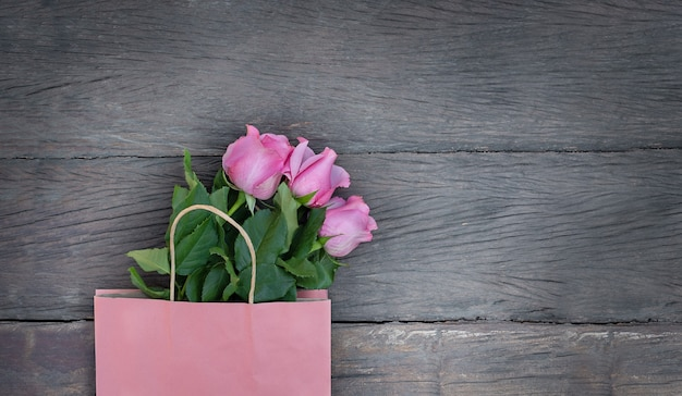 Saco de papel rosa e rosas cor de rosa em fundo de madeira