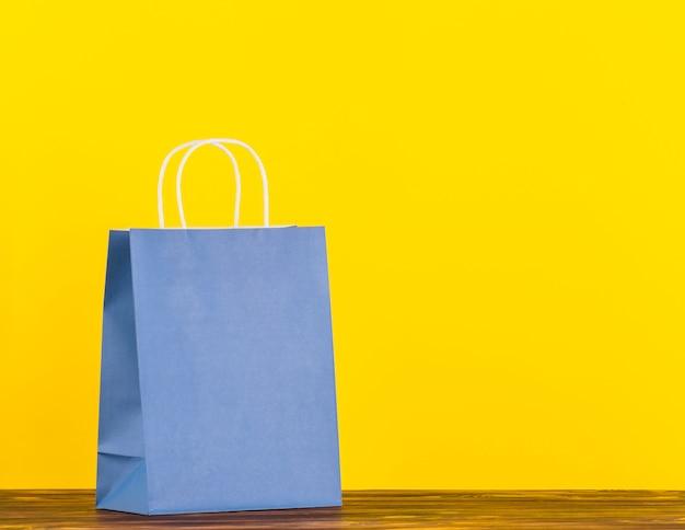 Saco de papel único azul na superfície de madeira com pano de fundo amarelo