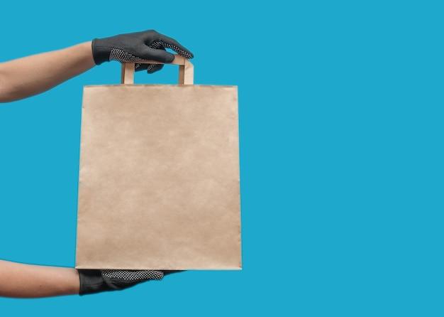 Saco de papel vazio. saco de compras para mantimentos. mãos em luvas pretas.