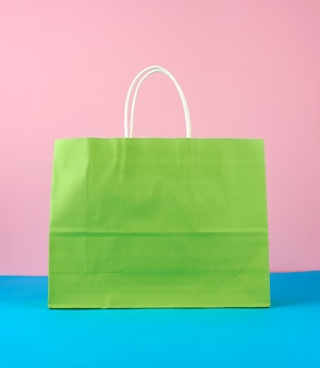 Saco de papel verde vazio com alças brancas para compras e presentes