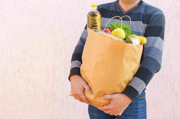 Saco de papelão com produtos. conceito de homem engajado na caridade.