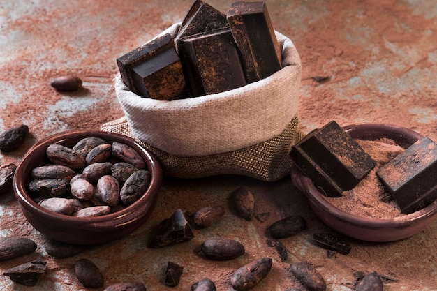 Saco de pedaços de barra de chocolate e cacau em pó e feijão na mesa bagunçada