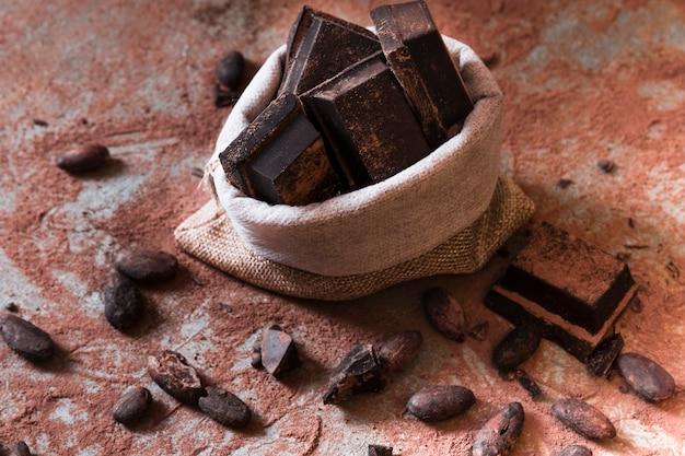 Saco de pedaços de barra de chocolate e cacau em pó e feijão na mesa