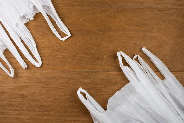 Saco de plástico branco com fundo de madeira. reduza o conceito de reciclagem de reutilização.