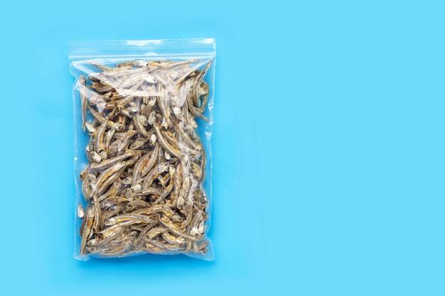 Saco de plástico de anchovas secas sobre fundo azul.