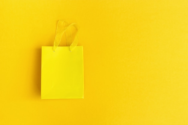 Saco de presente amarelo em fundo de papel amarelo