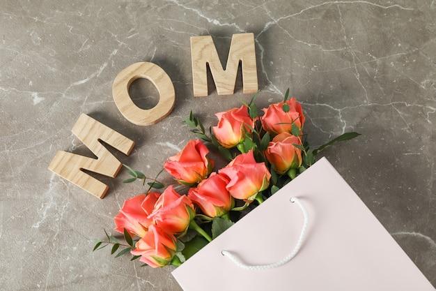 Saco de presente com buquê de rosas laranja e inscrição mãe na mesa marrom, vista superior