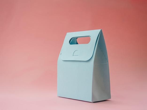 Saco de presente de papel azul na superfície rosa