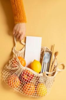 Saco de rede reutilizável cheio de frutas e utensílios de viagem ecológicos