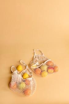 Saco de rede reutilizável com frutas em um fundo laranja