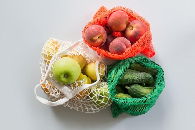 Saco de rede três compras com frutas e legumes.
