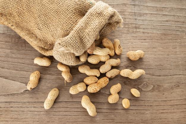 Saco de serapilheira e amendoins na mesa de madeira rústica. arachis hypogaea