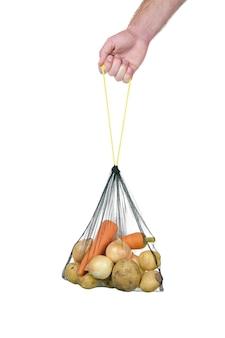 Saco de supermercado eco com legumes na mão em branco