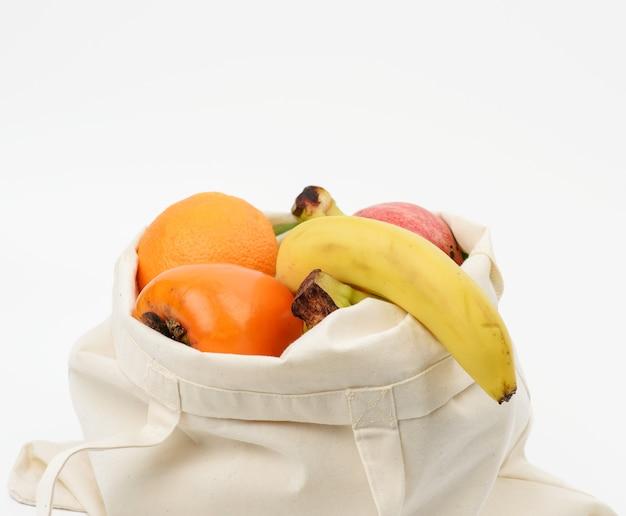 Saco de tecido bege com frutas frescas em uma superfície branca, desperdício zero
