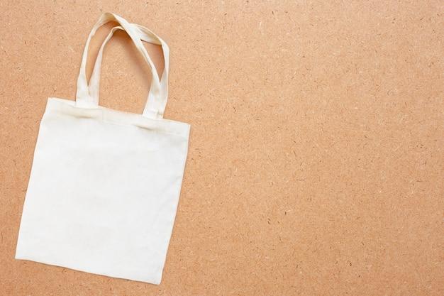 Saco de tecido branco em madeira compensada.