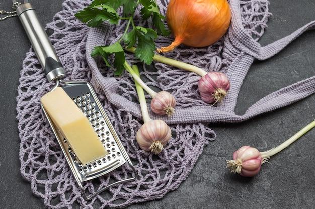 Saco de tecido de malha com mantimentos. alho, cebola e queijo no ralador, raminho de salsa. fundo preto. vista do topo