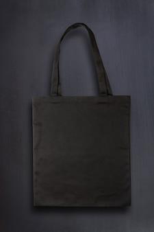 Saco de tecido preto em branco contra o fundo do quadro-negro