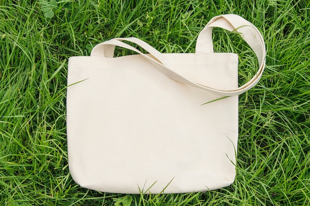 Saco de tecido têxtil eco, limpo, lugar para texto, maquete. vista superior, fundo de grama verde.