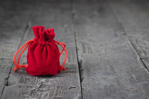 Saco de tecido vermelho brilhante sobre uma mesa de madeira escura.