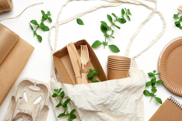 Saco de têxteis e talheres descartáveis de papel artesanal marrom, folhas de hortelã verde