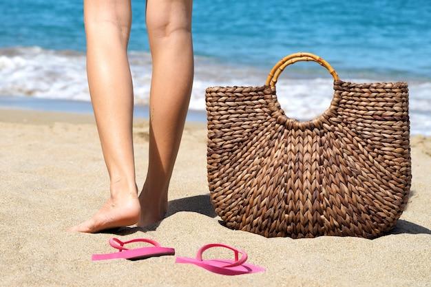 Saco de vime na praia e sandálias de uma jovem mulher